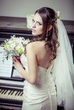 Junge schöne Braut, die Blumenstrauß von Blumen hält. Stockfoto