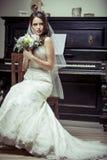 Junge schöne Braut, die Blumenstrauß von Blumen hält. Lizenzfreies Stockbild