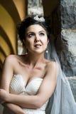 Junge schöne Braut, die an der Felsenwand sich lehnt Lizenzfreie Stockfotografie