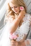 Junge schöne Braut, die eine kleine Rosarosenknospe repariert stockfotos