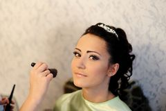 Junge schöne Braut, die Hochzeitsmake-up anwendet Stockfotos