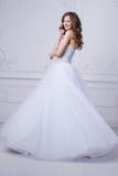 Junge schöne Braut, die im antiken dekorativen InnenDesign erfolgt mit Formteile steht Schönes Tanzen der jungen Frau der Paare Lizenzfreies Stockbild