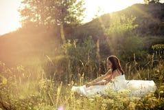 Junge schöne Braut, die im grünen Gras liegt Stockbild