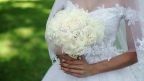 Junge schöne Braut in heiratendem weißem Kleid mit Blumenstrauß von den weißen Rosen, die in einem Park am Sommertag bleiben stock footage