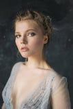 Junge schöne Braut im Hochzeitskleid, das im Studio aufwirft Stockbild