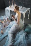 Junge schöne Braut im Hochzeitskleid, das im Studio aufwirft Lizenzfreie Stockfotos