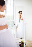 Junge schöne Braut, zum ihres Kleides zu versuchen Stockfotografie