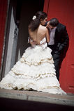 Junge schöne Brautpaare, die gegen rotes Gebäude küssen Stockfoto