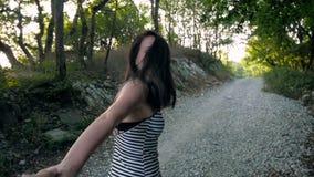 Junge schöne Brunette-Frau, die eigenhändig ihren Liebhaber auf Gebirgsstraße, Follow-mekonzept führt stock footage