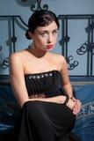 Junge schöne Brunettefrau, die auf Bett sitzt Lizenzfreies Stockfoto