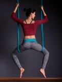 Junge schöne Brunettefrau, die Fliegenyoga tut Sitzen im hammoc Stockfotos