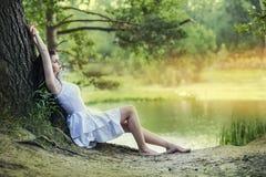 Junge schöne Brunettefrau, die im Wald sitzt und stillsteht stockfotografie
