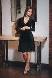 Junge schöne Brunettefrau im schwarzen Kleid Stockbilder
