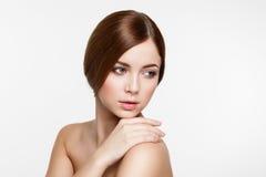 Junge schöne Brunettefrau mit natürlichem Make-up auf grauem backg Stockfoto