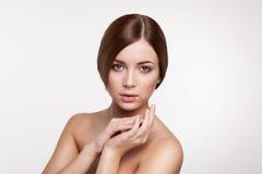 Junge schöne Brunettefrau mit natürlichem Make-up auf grauem backg Stockfotos