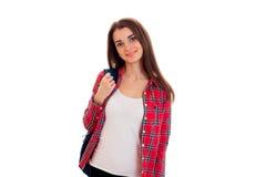 Junge schöne Brunettestudentenfrau mit blauem Rucksack auf ihrer Schulter, welche die Kamera und das Lächeln an lokalisiert betra Lizenzfreie Stockfotos
