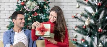 Junge schöne Causacian-Paare, offene Geschenkbox der Frau, sitzend stockbild