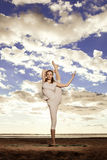 Junge schöne dünne Frau übt Yoga auf dem Strand an den sunris Stockfotografie