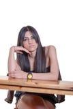 Junge schöne Dame, die hinten von einem hölzernen Schreibtisch sitzt Lizenzfreie Stockfotos