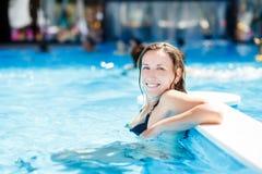 Junge schöne Dame, die im Swimmingpool sich entspannt Lizenzfreies Stockbild