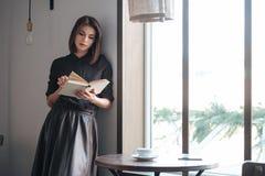Junge schöne Dame, die nahes Fenster im Café steht Lizenzfreies Stockfoto
