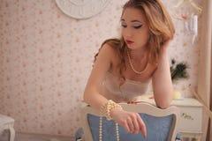 Junge schöne Dame mit Puppengesicht und dem gelockten Haar in der sinnlichen Pastellwäsche zu Hause auf Stuhl Stockbild