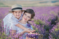 Junge schöne Damenmutter mit der reizenden Tochter, die auf das Lavendelfeld an einem Wochenendentag in den wunderbaren Kleidern  Lizenzfreie Stockfotos
