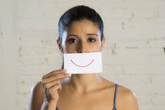 Junge schöne deprimierte Frau, die ihre Sorge und Traurigkeit hinter einem Papier mit einem gezogenen Lächeln versteckt Lizenzfreie Stockfotografie