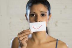 Junge schöne deprimierte Frau, die ihre Sorge und Traurigkeit hinter einem Papier mit einem gezogenen Lächeln versteckt Stockfotos