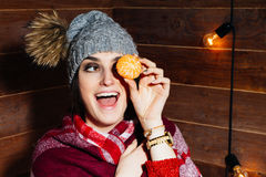 Junge schöne dunkelhaarige Frau, die in der Winterkleidung und -kappe mit Tangerinen auf hölzernem Hintergrund lächelt Lizenzfreies Stockfoto
