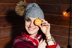 Junge schöne dunkelhaarige Frau, die in der Winterkleidung und -kappe mit Tangerinen auf hölzernem Hintergrund lächelt Stockfotos