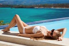 Junge schöne ein Sonnenbad nehmende Frau Nette Seeansicht Lizenzfreie Stockfotografie
