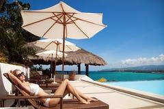 Junge schöne ein Sonnenbad nehmende Frau Nette Seeansicht Lizenzfreie Stockbilder