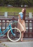 Junge schöne, elegant gekleidete Frau mit dem Fahrrad im Freien lizenzfreies stockbild