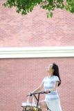 Junge schöne, elegant gekleidete Frau mit dem Teilen des Fahrrades Schönheit, Mode und Lebensstil Lizenzfreies Stockbild