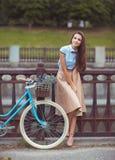 Junge schöne, elegant gekleidete Frau mit Fahrrad stockfotos