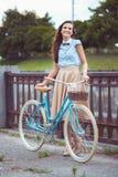 Junge schöne, elegant gekleidete Frau mit Fahrrad lizenzfreie stockfotografie