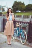 Junge schöne, elegant gekleidete Frau mit Fahrrad lizenzfreies stockfoto