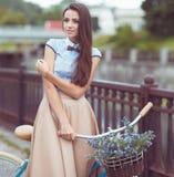 Junge schöne, elegant gekleidete Frau mit Fahrrad stockfoto