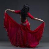 Junge schöne exotische Ostfrauen führt Bauchtanz im ethnischen roten Kleid mit offenem Rücken auf grauem Hintergrund durch Stockfoto