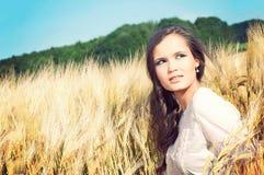 Junge schöne Frau auf dem goldenen Weizengebiet stockfotos