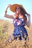 Junge schöne Frau auf einem Feld in der Sommerzeit Lizenzfreie Stockbilder