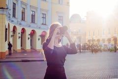 Junge schöne Frau in der Stadt mit Digitalkamera Stockfotos