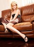 Junge schöne Frau, die auf Couch sitzt Stockfotografie