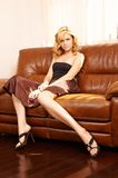 Junge schöne Frau, die auf Couch sitzt Stockbild