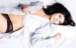 Junge schöne Frau, die auf dem Bett liegt Lizenzfreie Stockfotos