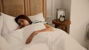 Junge schöne Frau, die auf dem Bett schläft Lizenzfreie Stockfotos