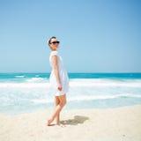 Junge schöne Frau, die auf dem Strand aufwirft Lizenzfreie Stockfotos