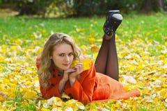 Junge, schöne Frau, die auf den Herbstblättern liegt Stockbild