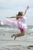 Junge schöne Frau, die auf den Strand springt. Lizenzfreies Stockfoto